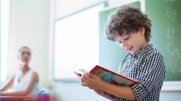 photo enfant lit un livre devant la classe