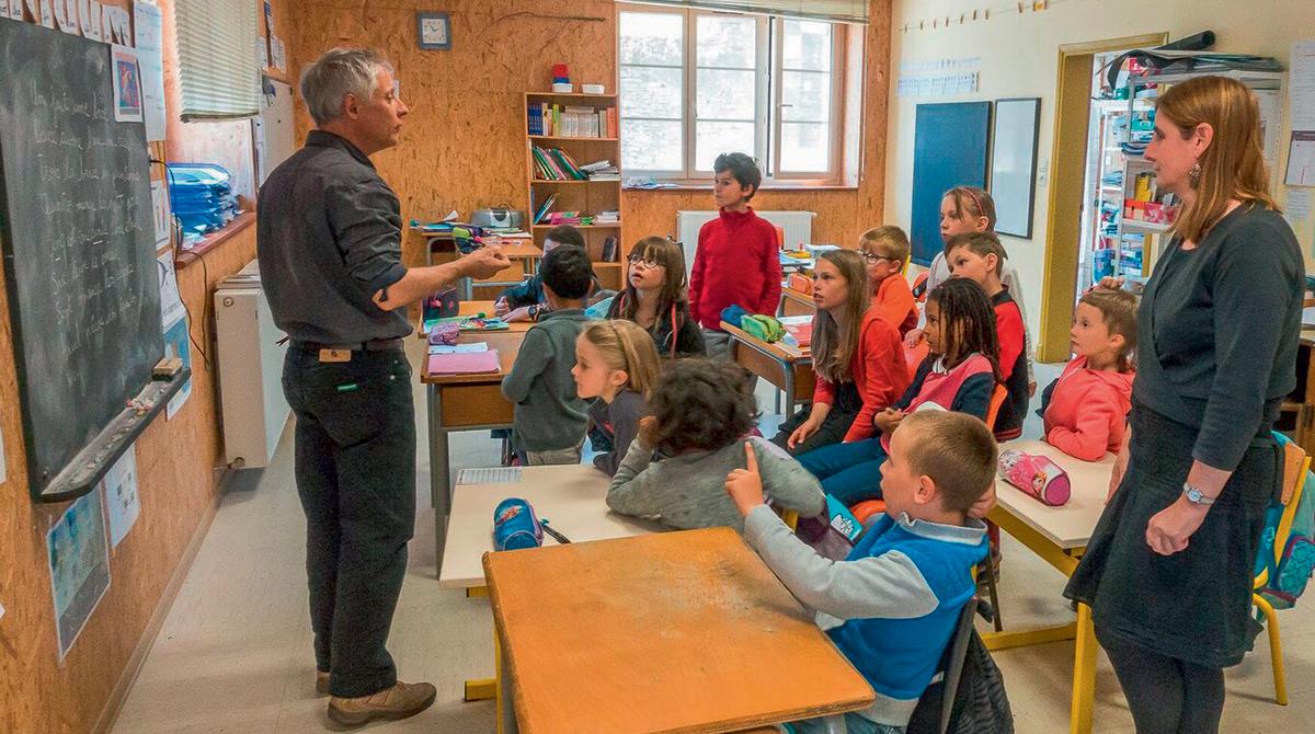 Gilles Brulet en pleine création poétique avec la classe unique de Sylvie Cros de l'école primaire, à Laval-Roquecezière (12). Photo: L. D. - J'aime lire n°489, octobre 2017.